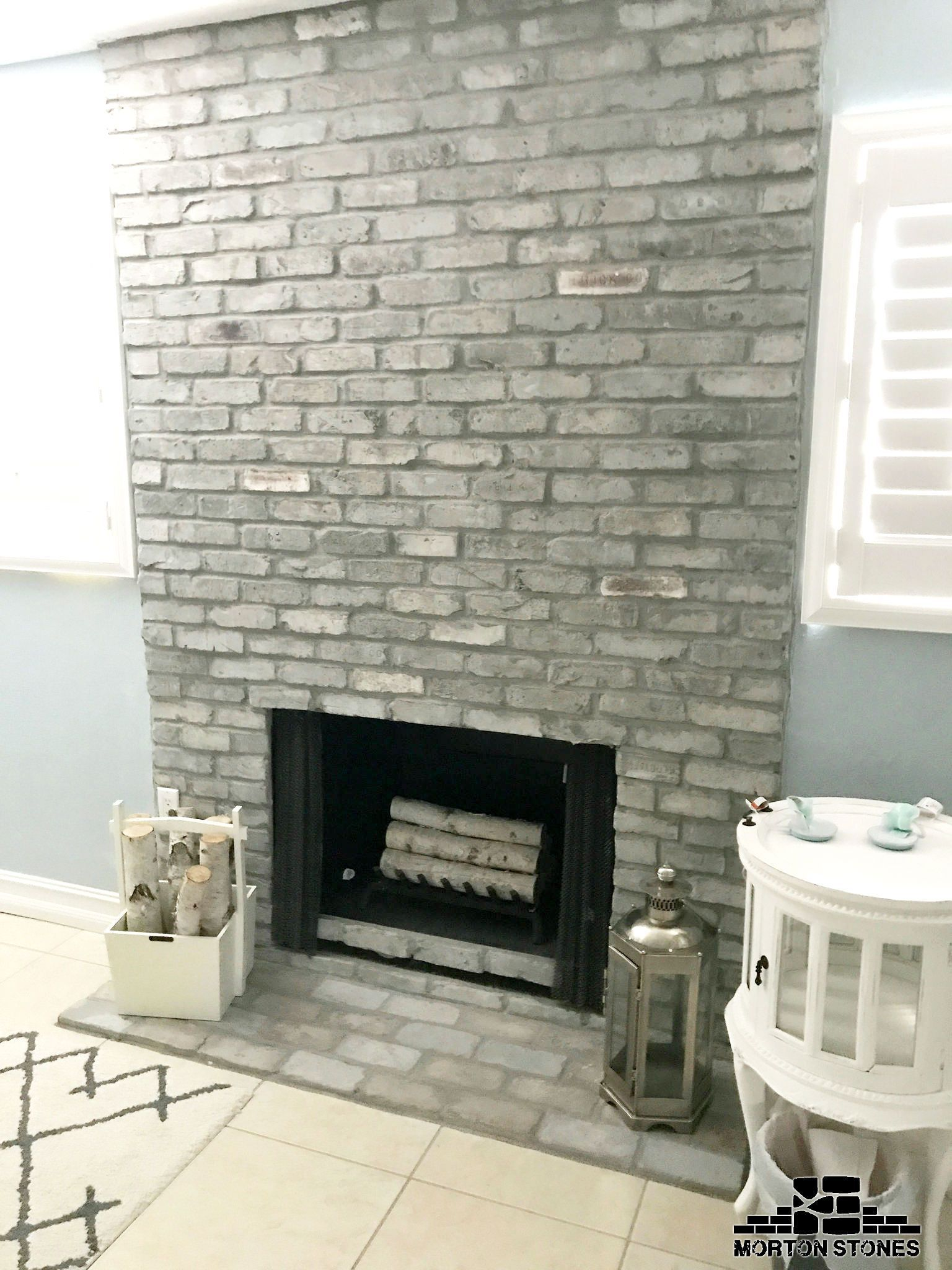 The Gray Brick Fireplace Adds A Lovely French Country Charm To The Room Mortonstones Brick Tiles Rustic Basement Remodeling Small Basement Remodel Remodel