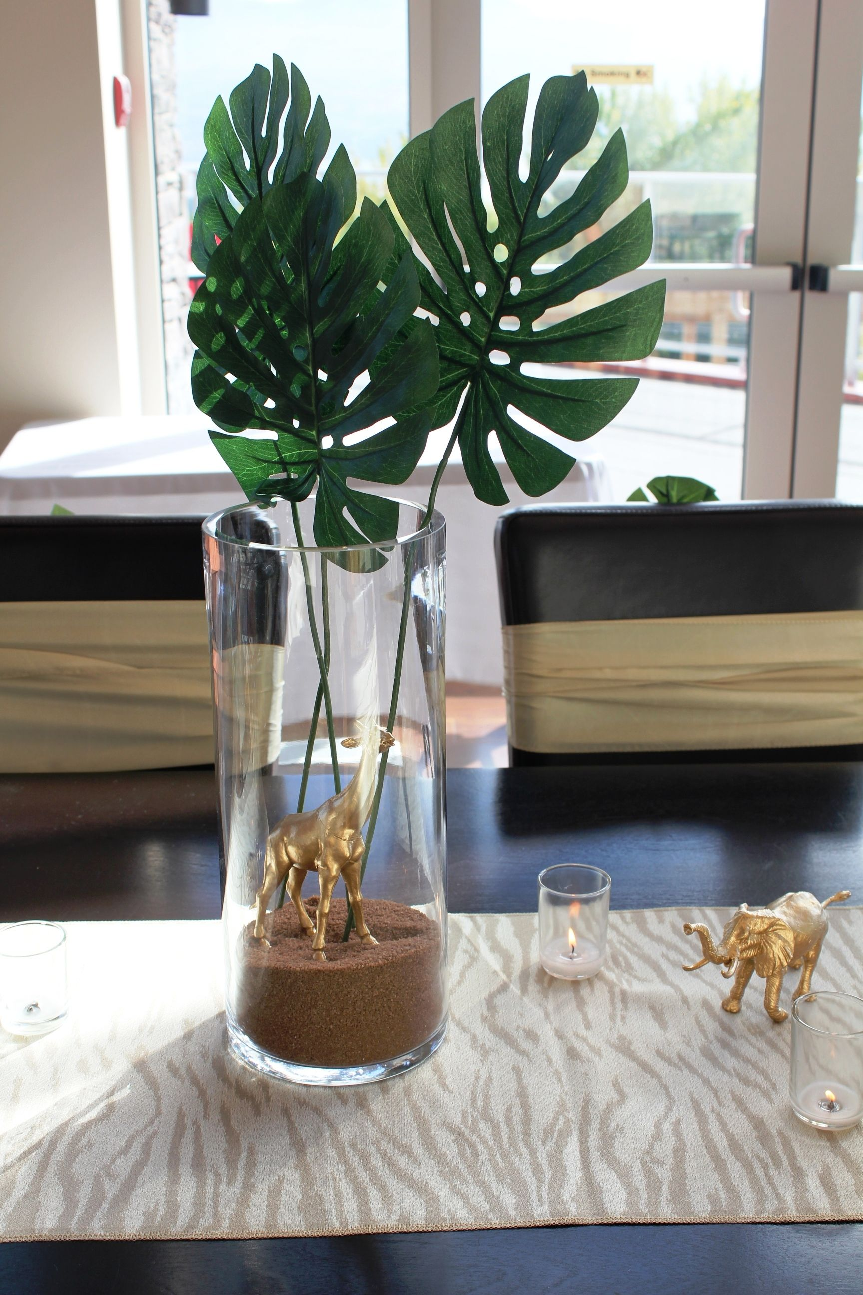 a cylinder vase filled with sand  safari leaves  and a giraffe makes for a simple  yet beautiful