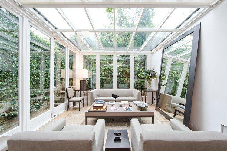 extension de maison avec toit en verre, canapé droit, table basse et
