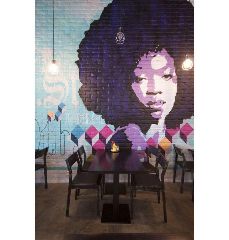 Feito em cima de uma parede de tijolos, o efeito feste grafite é bem diferente e coloriu todo o espaço com formas, letras e um retrato