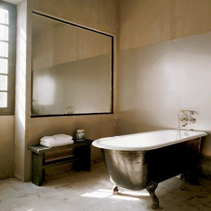 Salle de bains béton et zinc avec baignoire noire à pieds style