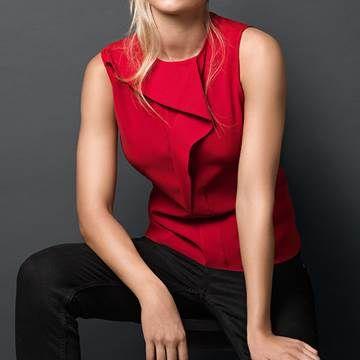 Nainen jolla on punainen pusero, joka on pesty AEG:n uusissa pesukoneissa