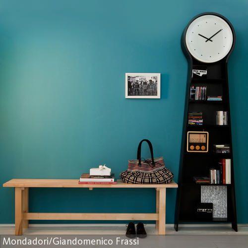 Schwarze Standuhr und hölzerne Sitzbank vor türkisfarbener Wand ...