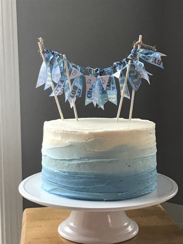 Simple boy baby shower cake with blue ombré and double ribbon banner.