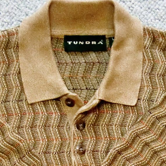 "Manufacturer: Tundra Canada  Size: Men's Large  Style: Short sleeve polo collar  Main colors: Golden tan  Yarn composition: 56% cotton, 44% polyester  Description: Vintage early 90's Canadian made Tundra men's size large short sleeve polo collar neck sweater. Marled golden tan in color with fancy zig-zag Coogi style knitting in a vertical pattern. There are small horizontal knits in orange, red, brown and black every ¾"" throughout. Excellent condition, doesn't appear to have been worn…"