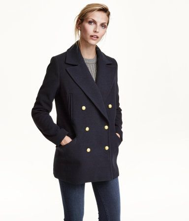 Double-breasted coat in felted woven fabric with a wide collar and lapels, handwarmer pockets, and side pockets with flap. Lined.