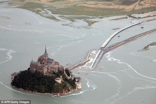 Mont Saint-Michel, in Normandy, is one of France's most famous landmarks. Wooden causeway was built in 1879 after natural one covered by seawater.