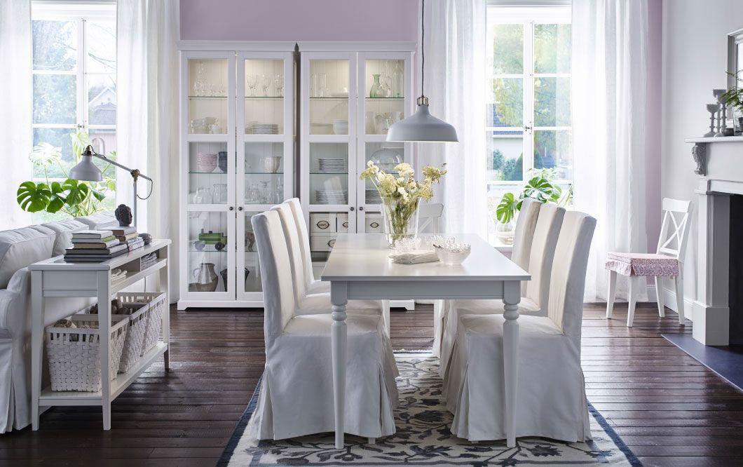 Zona pranzo con tavolo bianco e sedie con fodere in cotone bianco