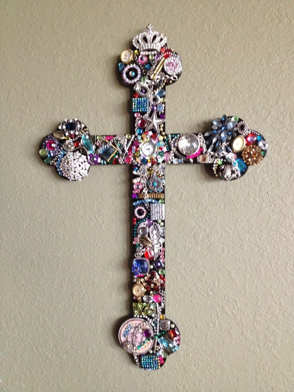 Custom Ordered 18 inch metal cross embellished with personal jewelry. stuckonsteel.com