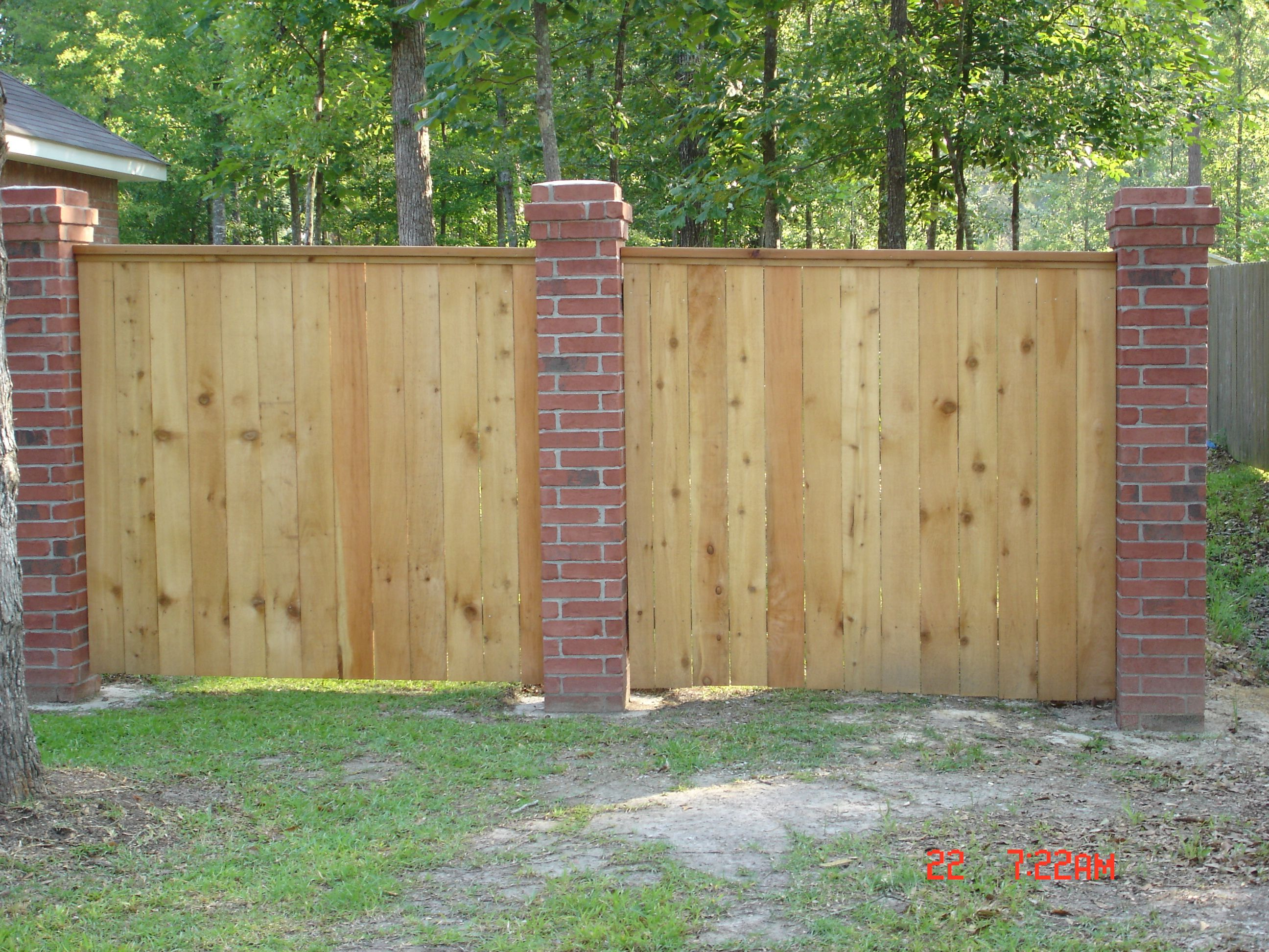 brick columns with wood fence brick columns brick fence on inexpensive way to build a wood privacy fence diy guide for 2020 id=22332