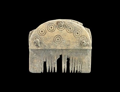 "Circa 9th-11th century CE. A D-shaped multipart bone comb comprising: two thin plates with sawn teeth, two D-shaped outer plates with ring-and-dot designs; three rivets securing. Bone, 18 grams, 56 mm (2 1/4"") Property of a London Gentleman; acquired before 1985.  A D-shaped multipart bone comb comprising: two thin plates with sawn teeth, two D-shaped outer plates with ring-an..."
