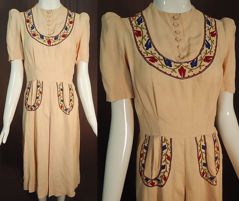 It is made of a yellowish cream color silk crepe de chine fabric, with red, blue and green chain stitch embroidery work flowers trimming the top and skirt pockets. This is truly a wonderful piece of wearable art!   eBay!