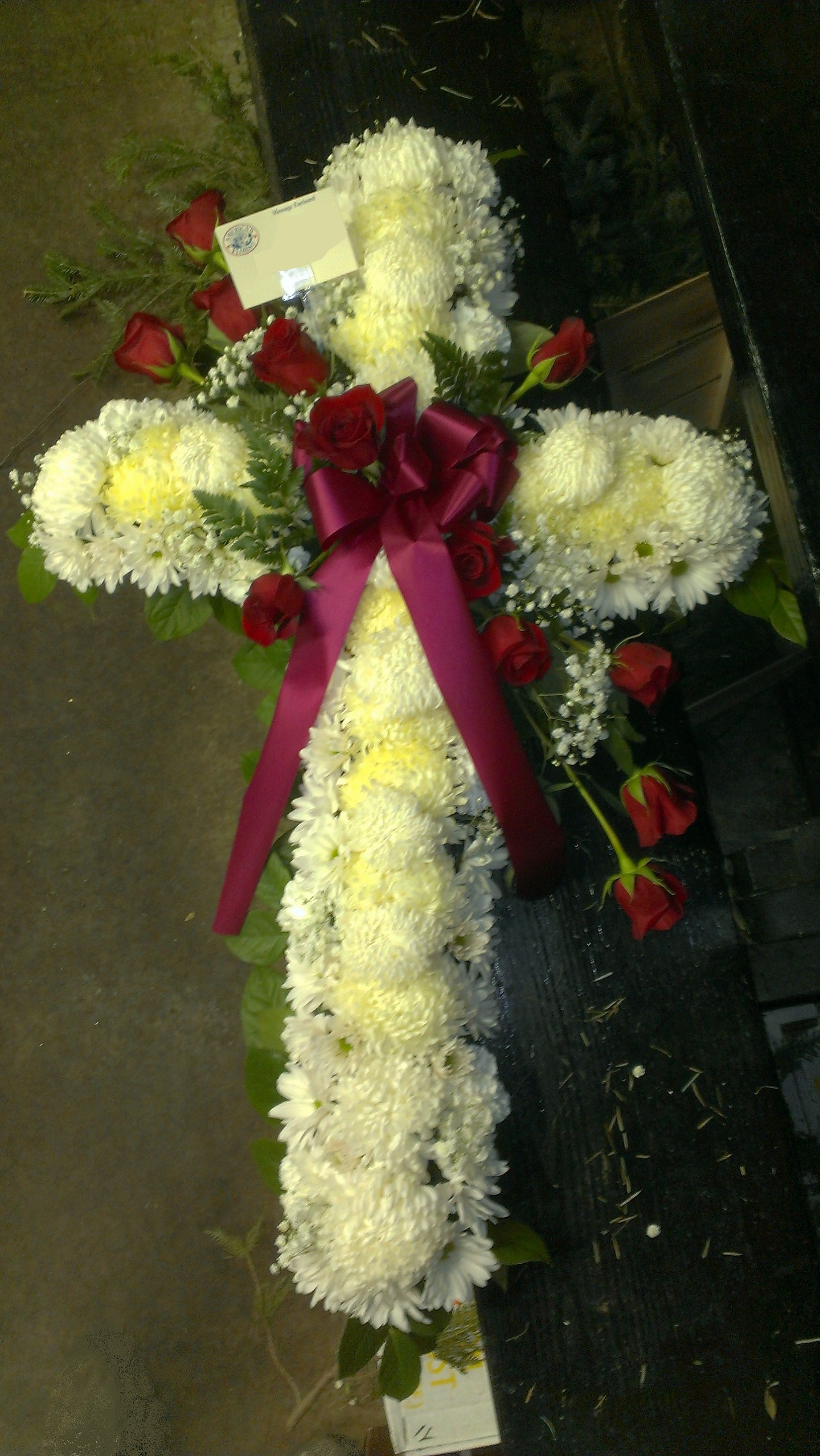White funeral cross very intricately decorated