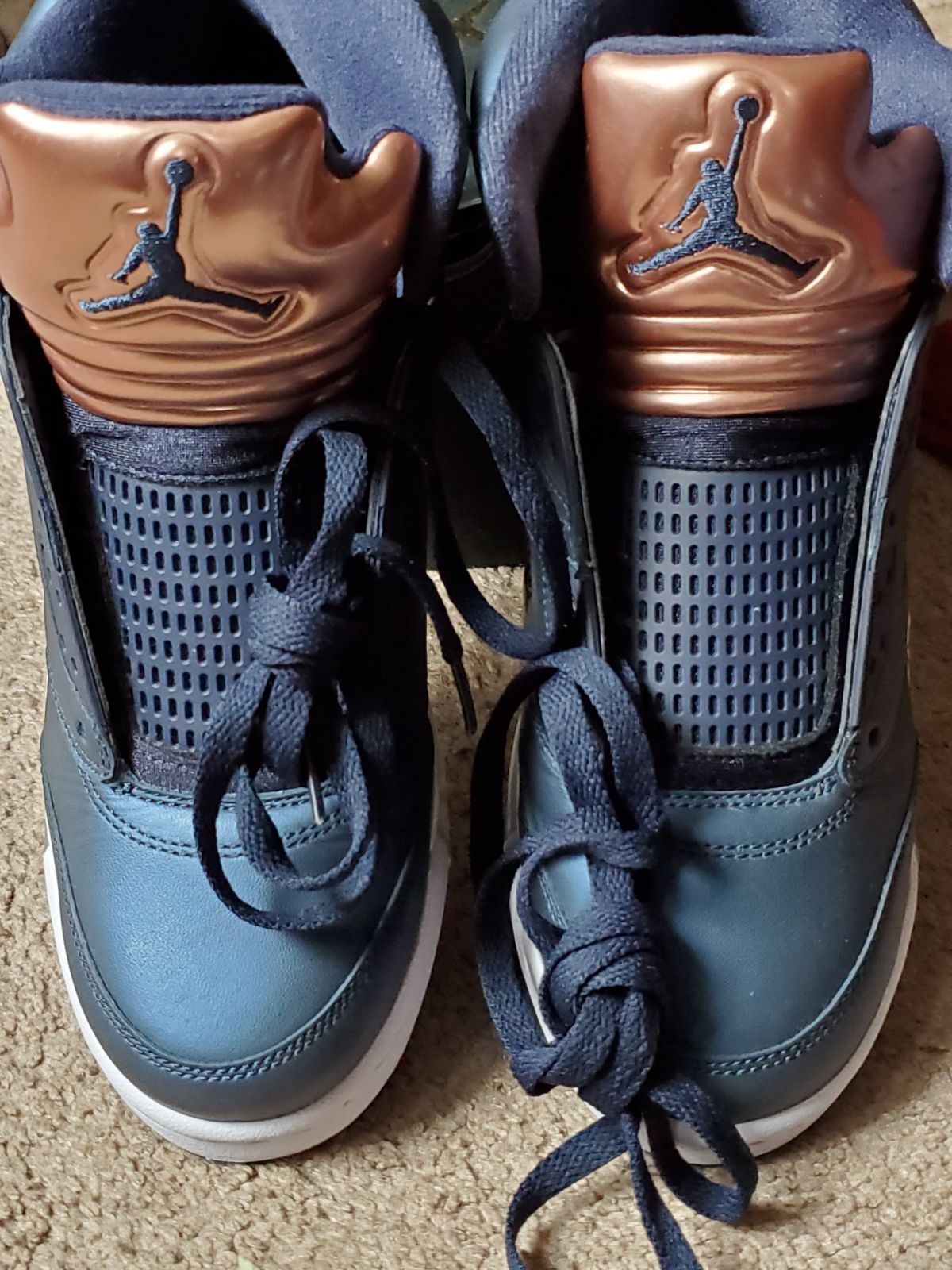 A pair of bronze blue and whiteair Jordan 5 retros brother wore one time not even a whole day his feet was hurting they're like new right shoe up top half a little scratch on them other than that they're nice. Jordans come with the original box come from a pet free clean home