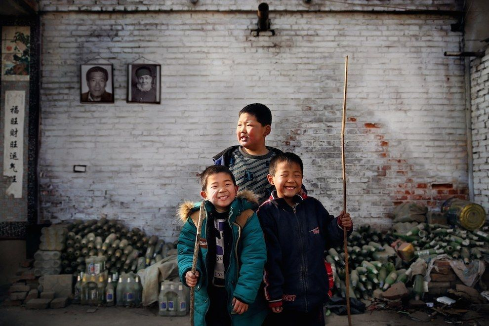 """Jaw-long (tallest) stands with his friends in front of his house in Nuguang village on the outskirts of Xingtai. The portraits behind depict his father and uncle who both worked in the nearby steel factory and died due to undiagnosed respiratory problems. Jaw-long has dropped out of school to help his mother with her glass recycling business."" - Photo by Souvid Datta"