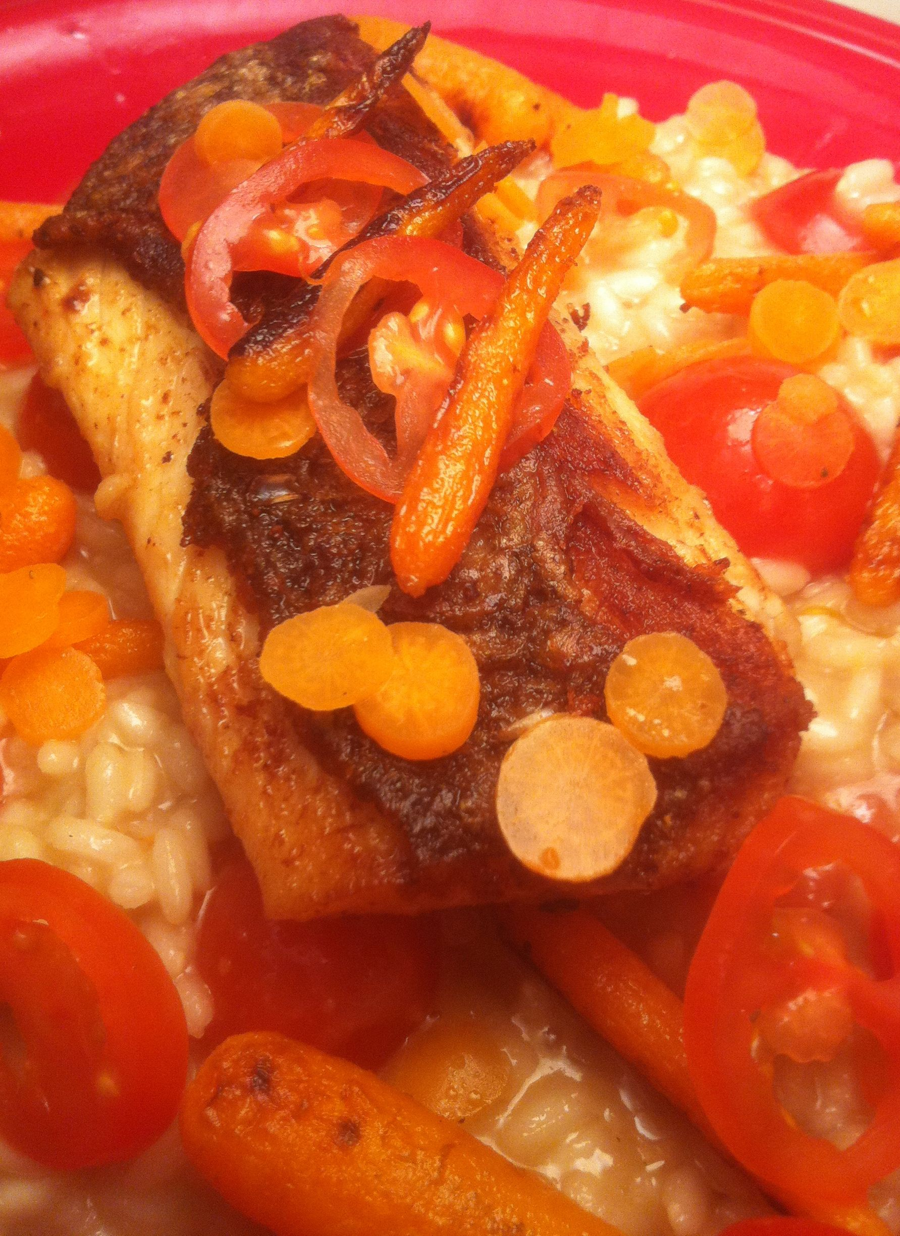 Striped bass on a white wine risotto with cherry tomatoes and baby carrots