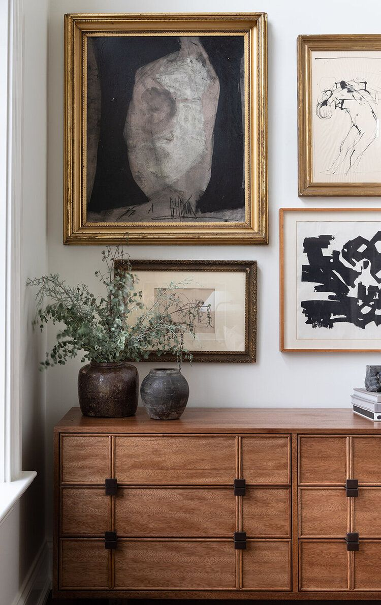 Organic vessels + vintage collection of frames + worldly living room + wooden sideboard + gold frames + pots and vases + book stacks + console styling | Haus Love