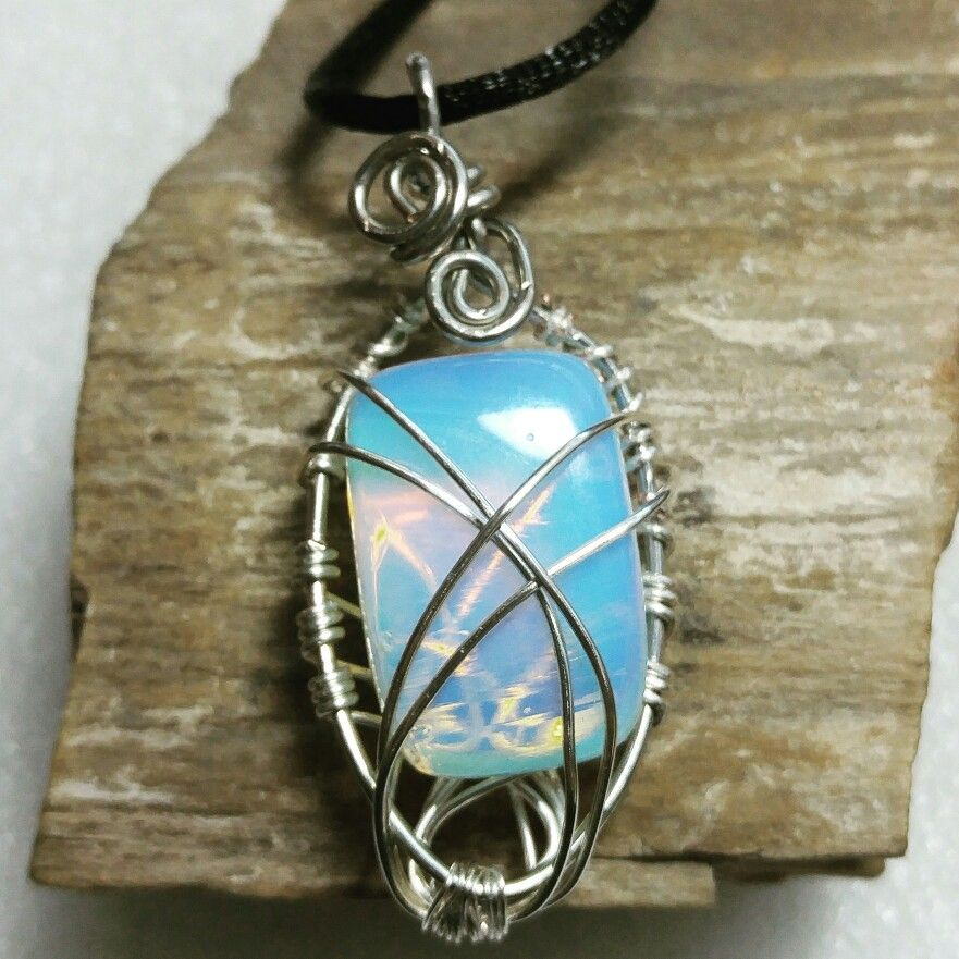 Silver caged opalite pendant on black rope necklace.