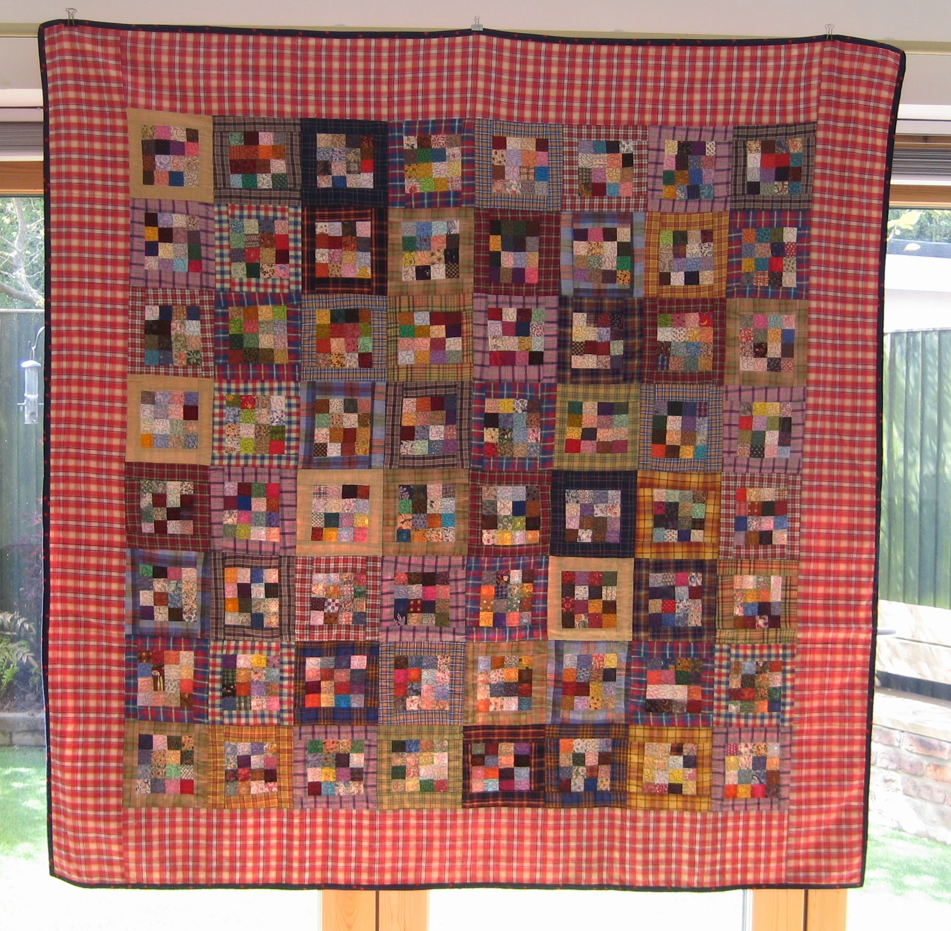 A picnic blanket quilt made from postage stamp sized fabric samples. Checked border. Vermichelli free motion quilted.