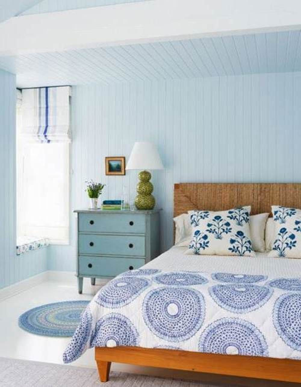 Mediumcolored wood furniture with cool blue tones in the bedroom