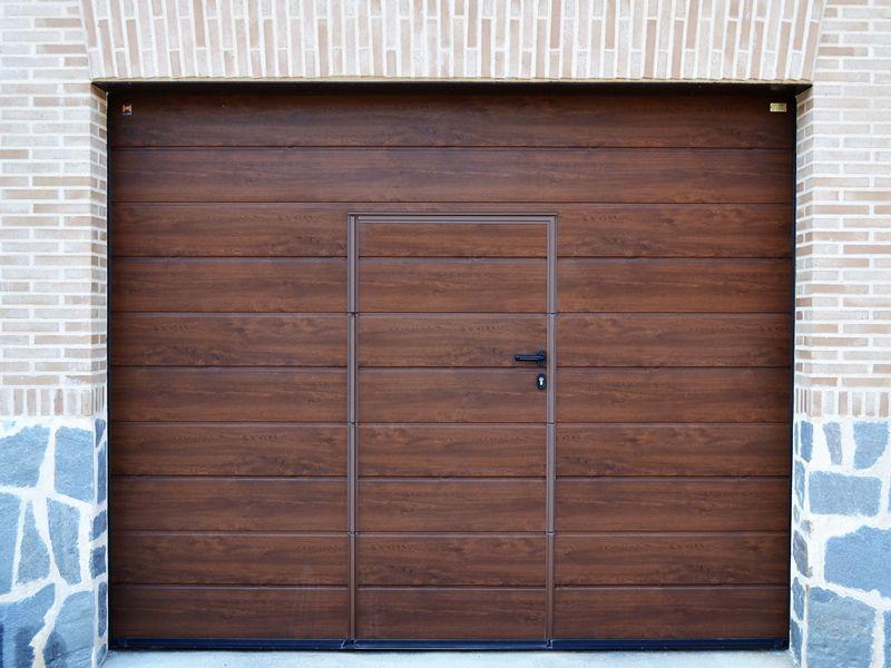 Puerta Seccional Hormann Con Puerta Peatonal Incorporada Acabado Madera Nogal Segurid Puertas De Garaje Puertas De Garaje De Madera Entrada De Casas Modernas