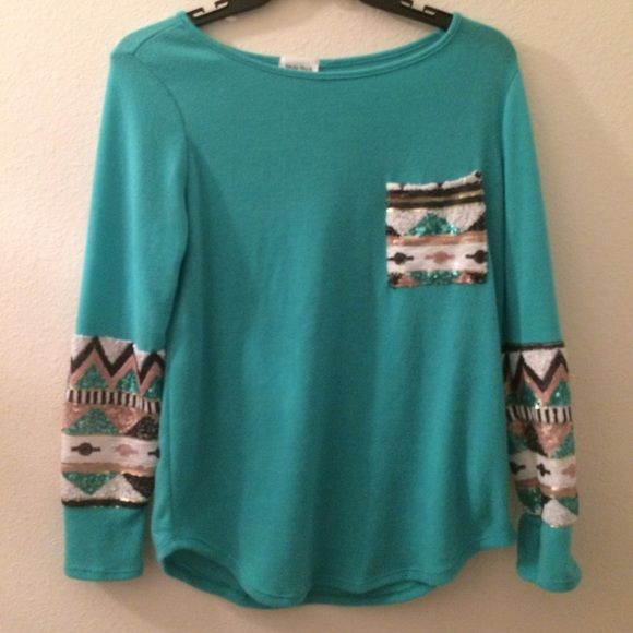 ! Teal aztec sequined sweater Purchased from a local boutique, never worn! Very vibrant pretty teal color and aztec printed sequins on chest pocket and towards the bottom of sleeves. Full length long sleeves. Brand is Style Rack. Size L, but will also fit a M (more loose). Material (Self- 95% ployester, 5% spandex) (Contrast- 100% polyester). Only blemish is pictured in 4th picture, a sequin got stuck on the sweater and made a little pull on the back but its very unnoticeable :) NO TRADES…