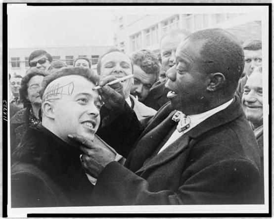 Louis Armstrong draws a trumpet and signs the side of a fans head. Nice, France,1961