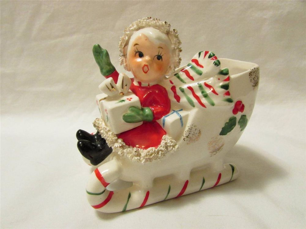 Vintage Napco ceramic Christmas shopper girl on on a candy cane sleigh planter.