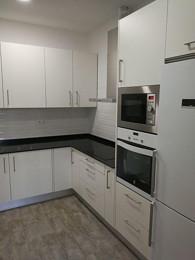 Cocina con muebles en color blanco, azulejo tipo metro en las