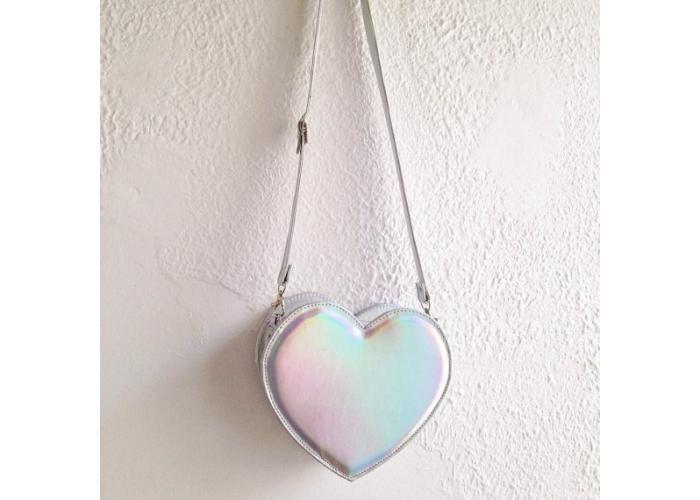 Bolsa en forma de corazon, hecha en piel sintetica holografica. Cierre y correa para colgar al hombro o cruzada. Medidas: 22 cm de…