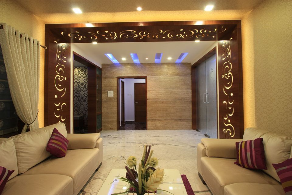 drawing room lighting. wooden panelling arund the opening and marble cladded wall on other side with concealed lights drawing room lighting i