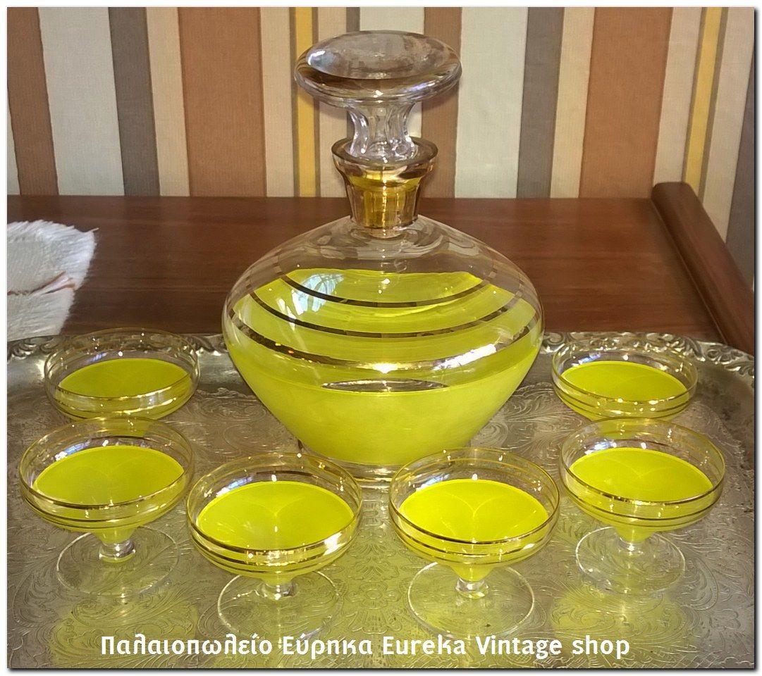 Σερβίτσιο ποτού σε διάφανο χρώμα με κίτρινη βαφή και χρυσές ρίγες, από την δεκαετία του 1950's. Σε άριστη κατάσταση.  Μπουκάλι και 6 σφηνάκια.  Ύψος μπουκαλιού 18εκ. ποτήρι 5εκ. άνοιγμα ποτηριού 6εκ.
