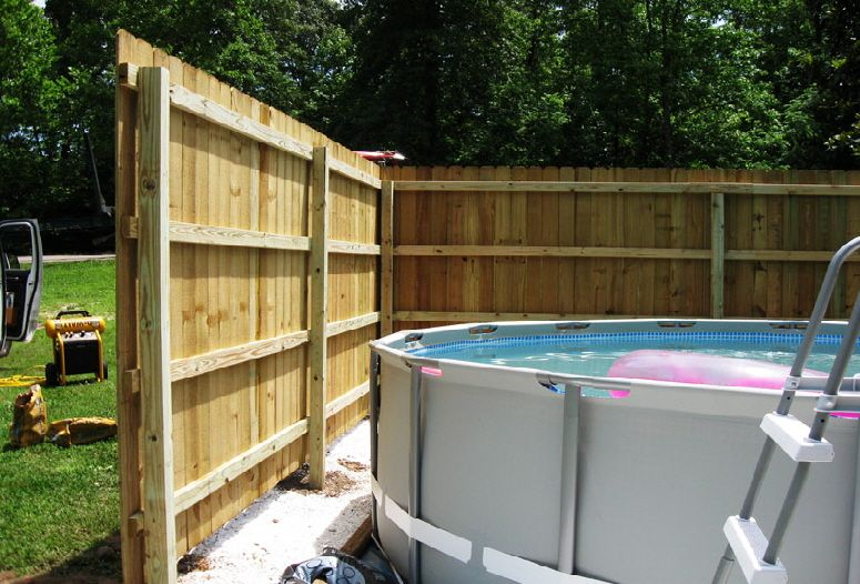 8 ft tall dog ear style wood privacy fence around an above ground pool