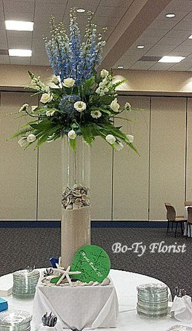 Food Table Arrangement For A Beach Themed Party Blue And White Flowers Sit On Top Of A Large Glas Beach Chic Weddings Silk Flowers Wedding Flower Arrangements