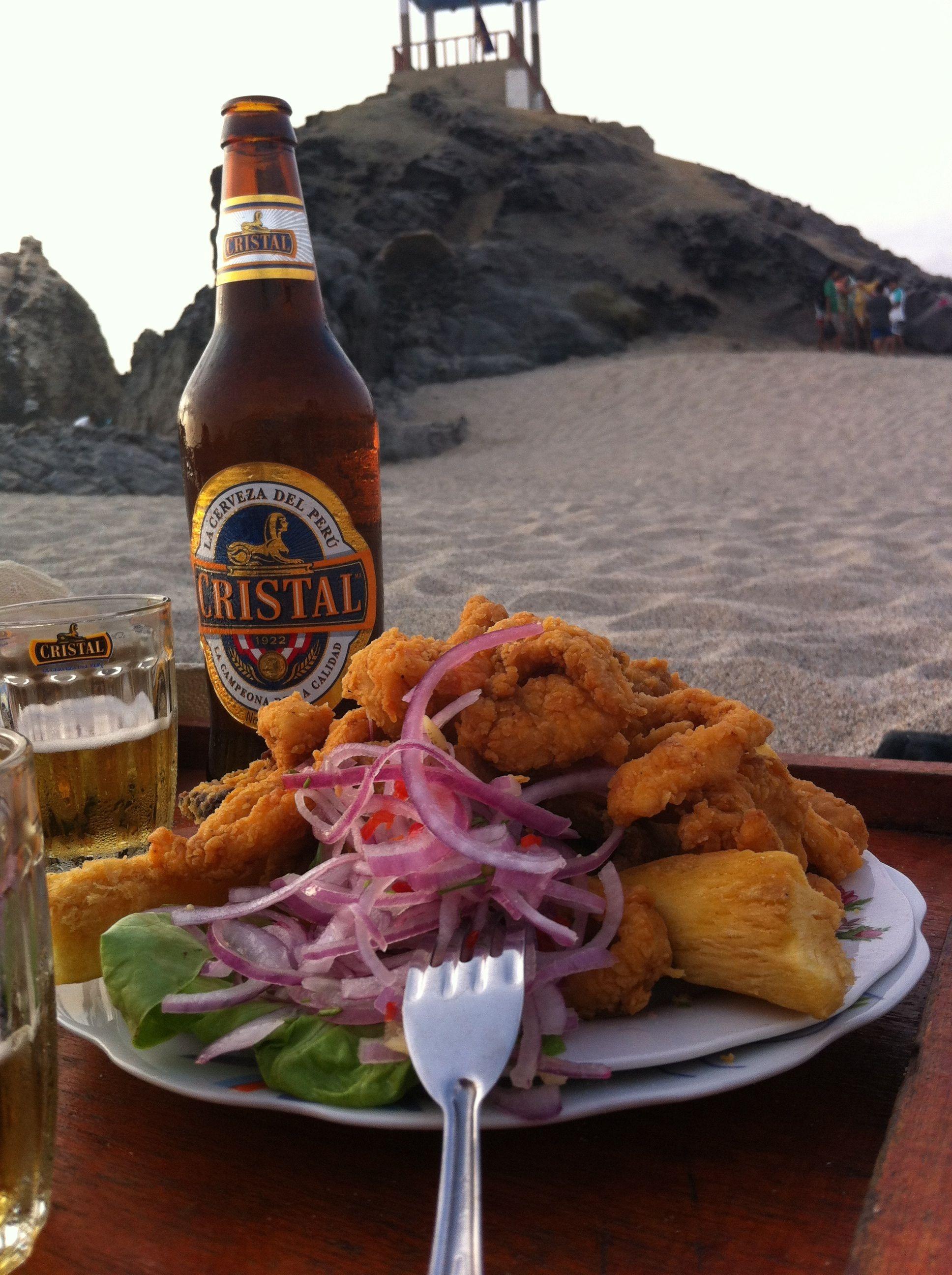 Plato De Jalea De Pescado Con Su Cerveza Cristal Con El Mirador De Punta Negra Al Fondo En La Playa La Peruvian Recipes Traditional Food International Recipes