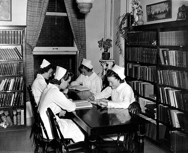 Four nurses hitting the books, while in uniform, during the 1950s.