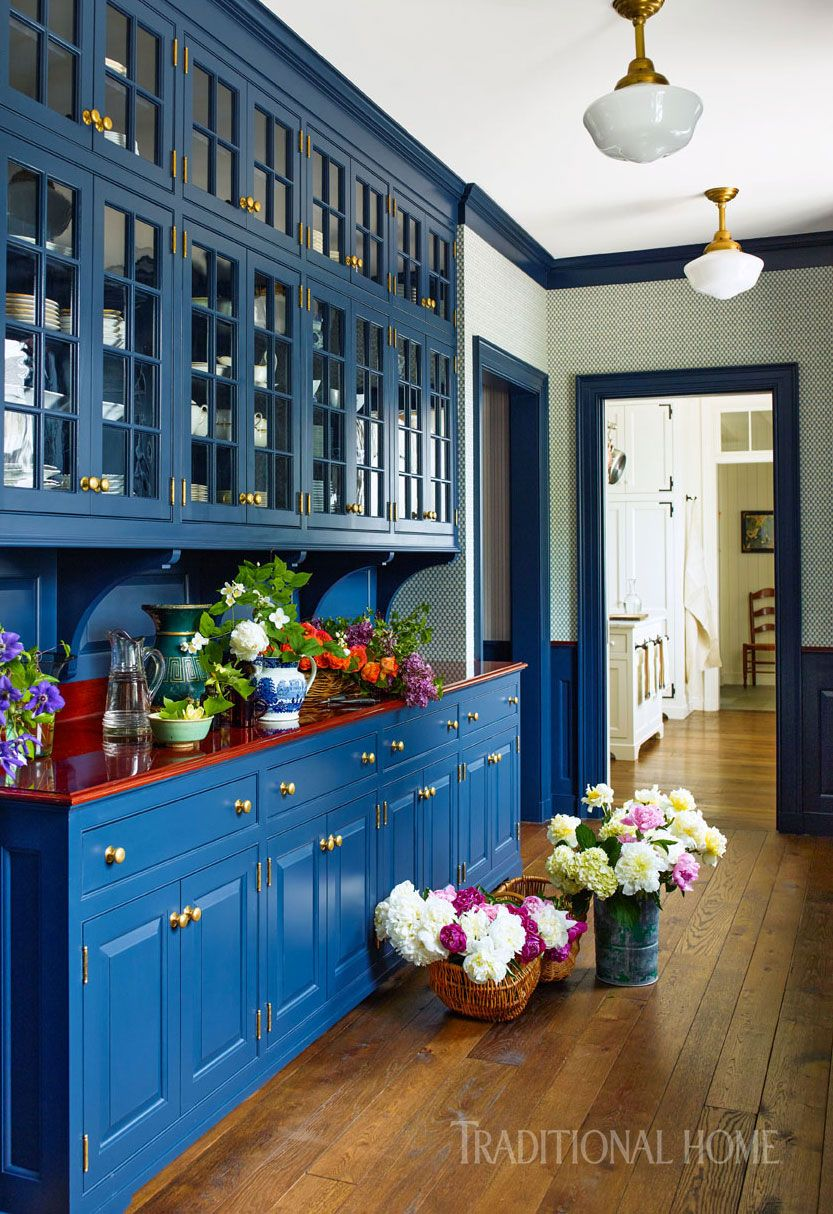 Bright blue-painted cabinetry with gold hardware contrasts yet ...