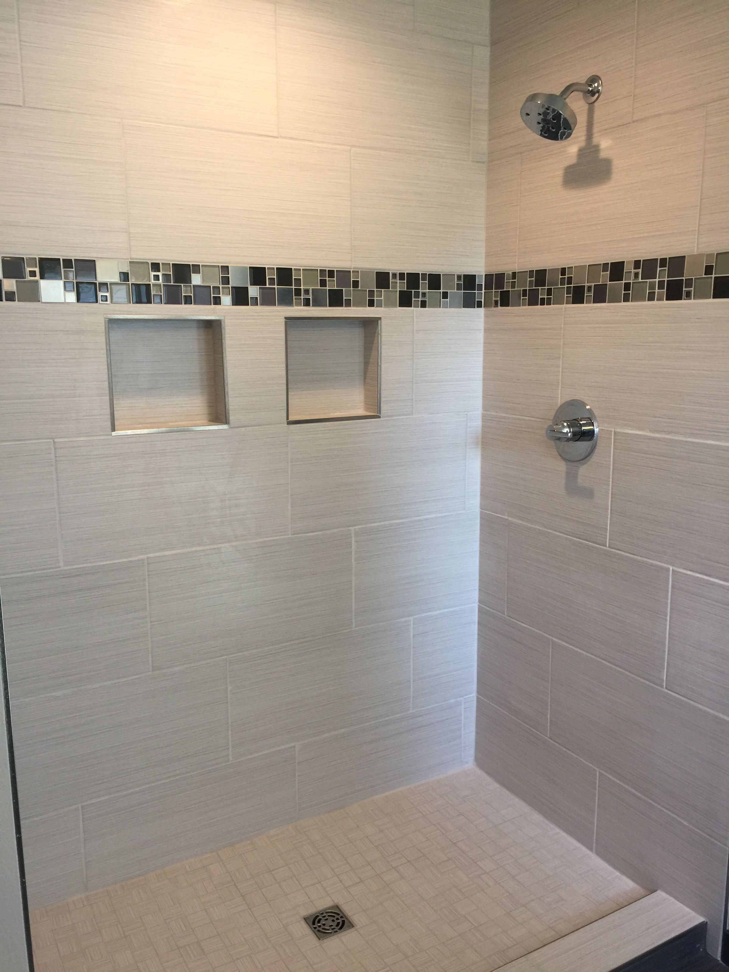 Custom Tiled Shower With 12x24 Satiated Tile Run 1/3 Staggered Vertically  With A Glass And Metal Mosaic Accent Strip.