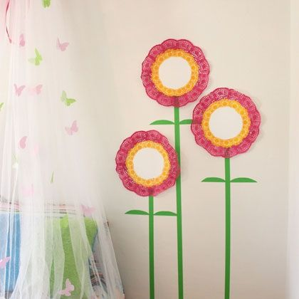 """Doily Flower Wall Art -Doilies aren't just for serving desserts anymore. Their pretty lace patterns are perfect for decorating, and on your wall, they make fanciful flowers. Add some green tape for stems and leaves, and your room becomes a garden of colorful creativity. -Doilies in two sizes (e.g., 14"""" and 8"""") - Acrylic paint - Spray adhesive - Green masking tape, 1"""" wide"""