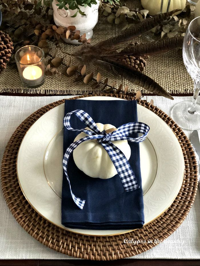 Thanksgiving Table Setting in a Navy Dining Room - Neutral table with pops of navy for Thanksgiving.  #thanksgivingtable #thanksgivingdecoration #gingham #blueandwhitedecor #tablesettings #whitepumpkins #thanksgivingtablesettings