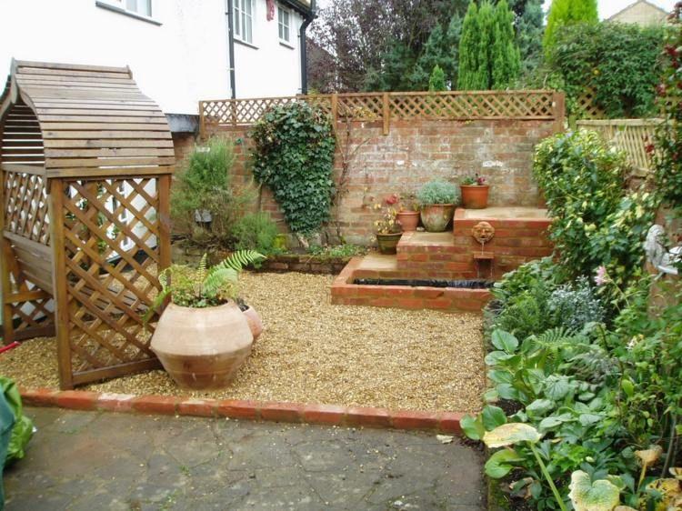 Garten Gestaltung Idee - Kieselsteinfläche mit Brunnen und - sitzplatz im garten mit steinmauer