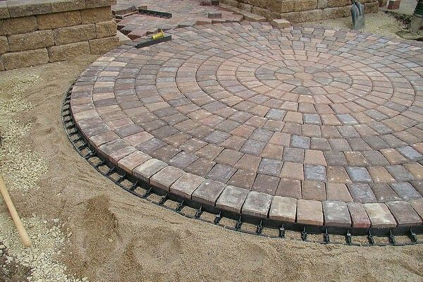 Pretty Circle Blending Into Sidewalk Proper Paxked Sand Amd Edge To Hold Pavers In Place Patio Pavers Design Paver Patio Interlocking Pavers