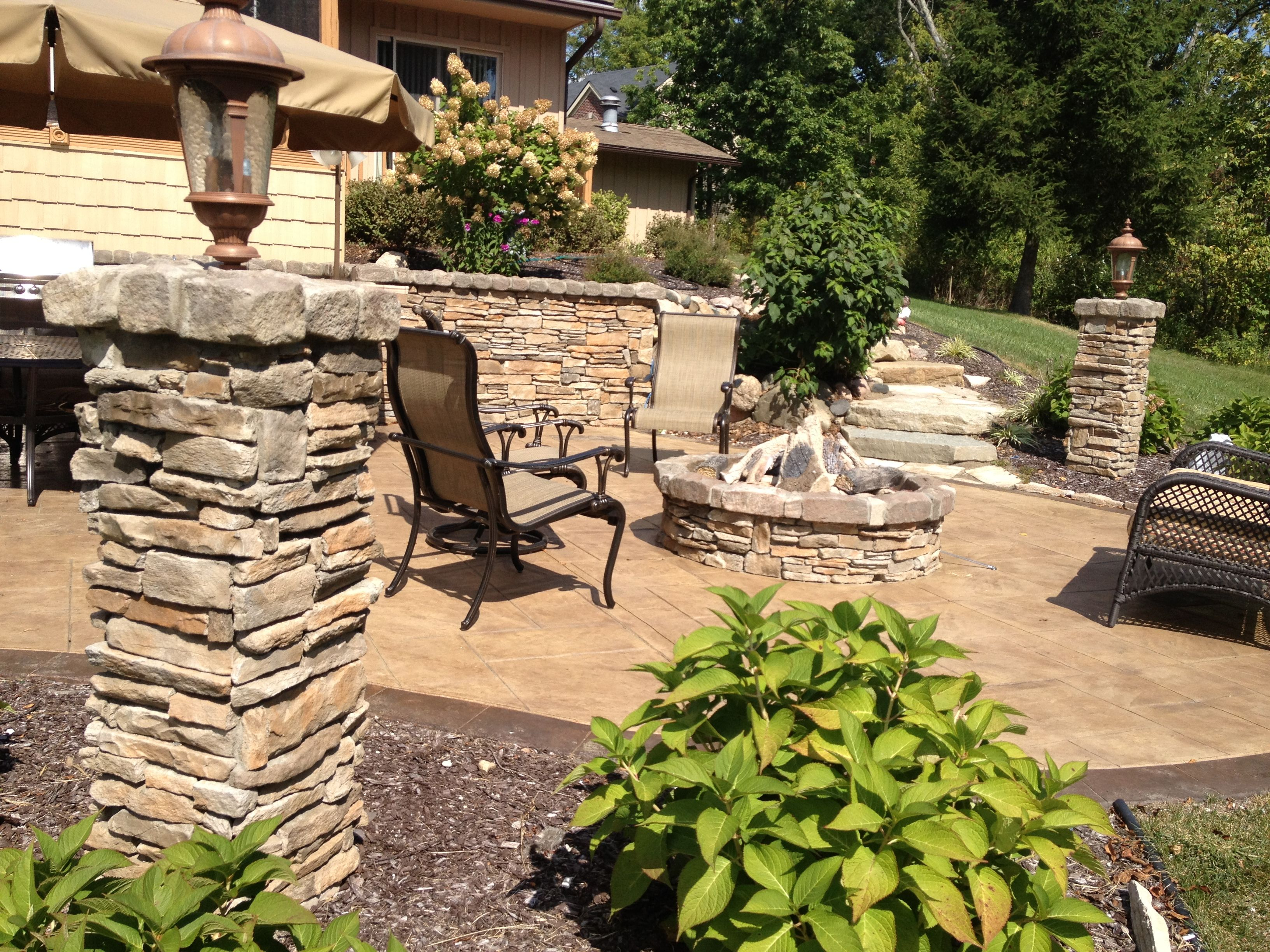 outdoor living cultured stone pillars stamped concrete gas remote