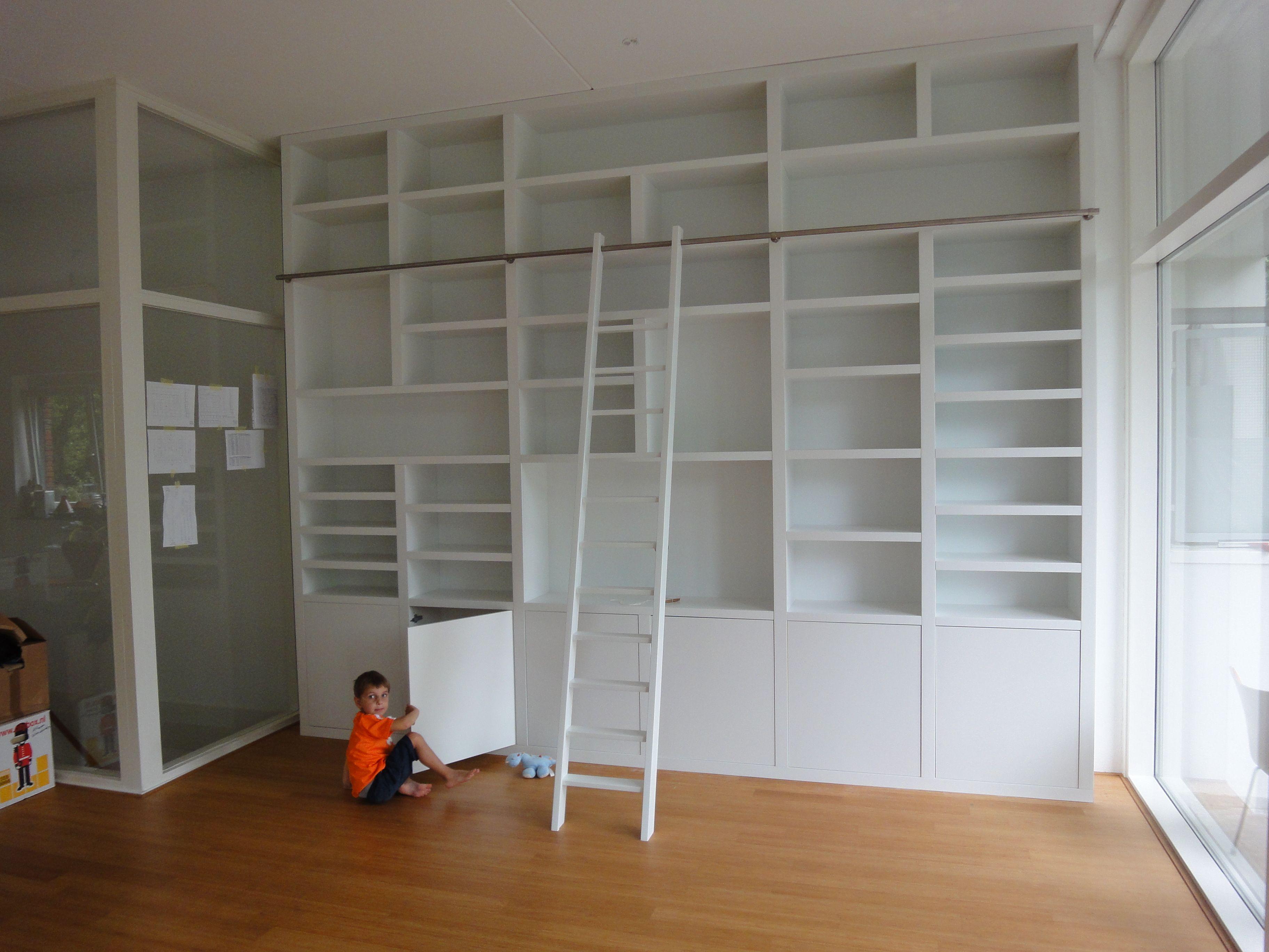Een moderne boekenkast in wit. Conventionele indeling met deuren ...
