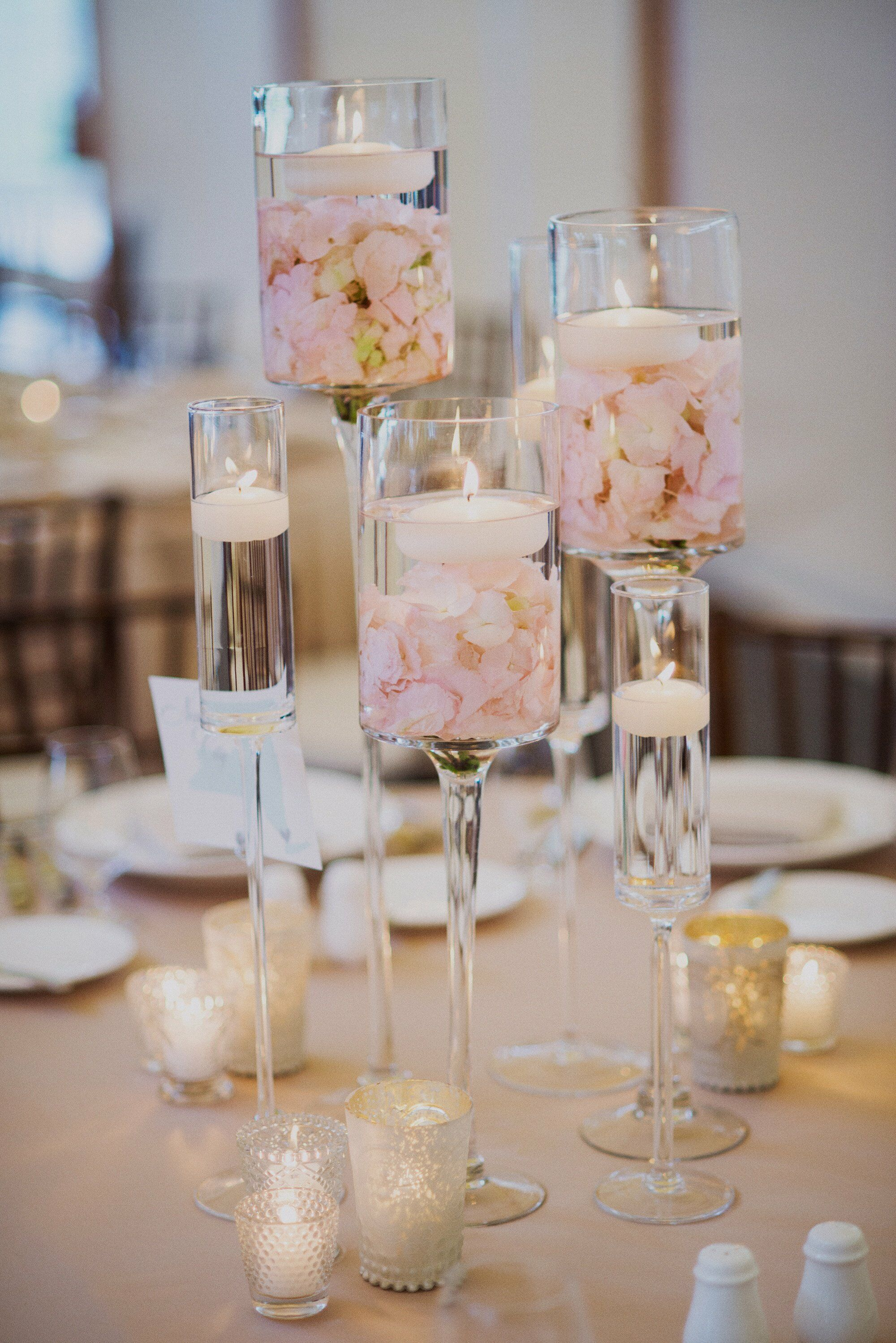 Clusters of stemmed hurricane vases filled with floating