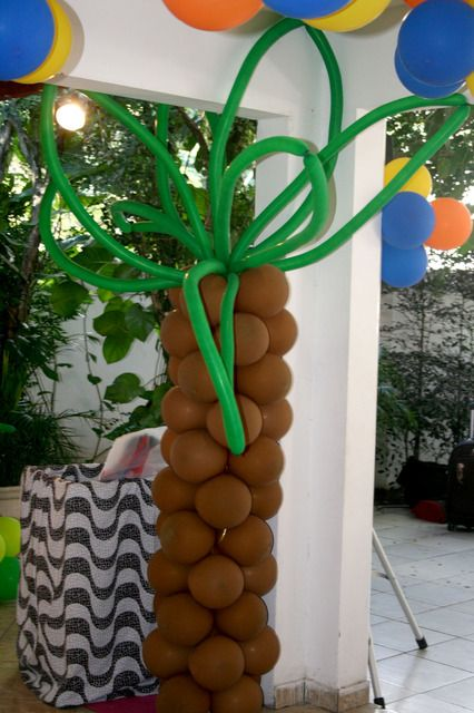 Create balloon palm trees for Rio movie party decorations - A unique outdoor movie night theming idea from Southern Outdoor Cinema.