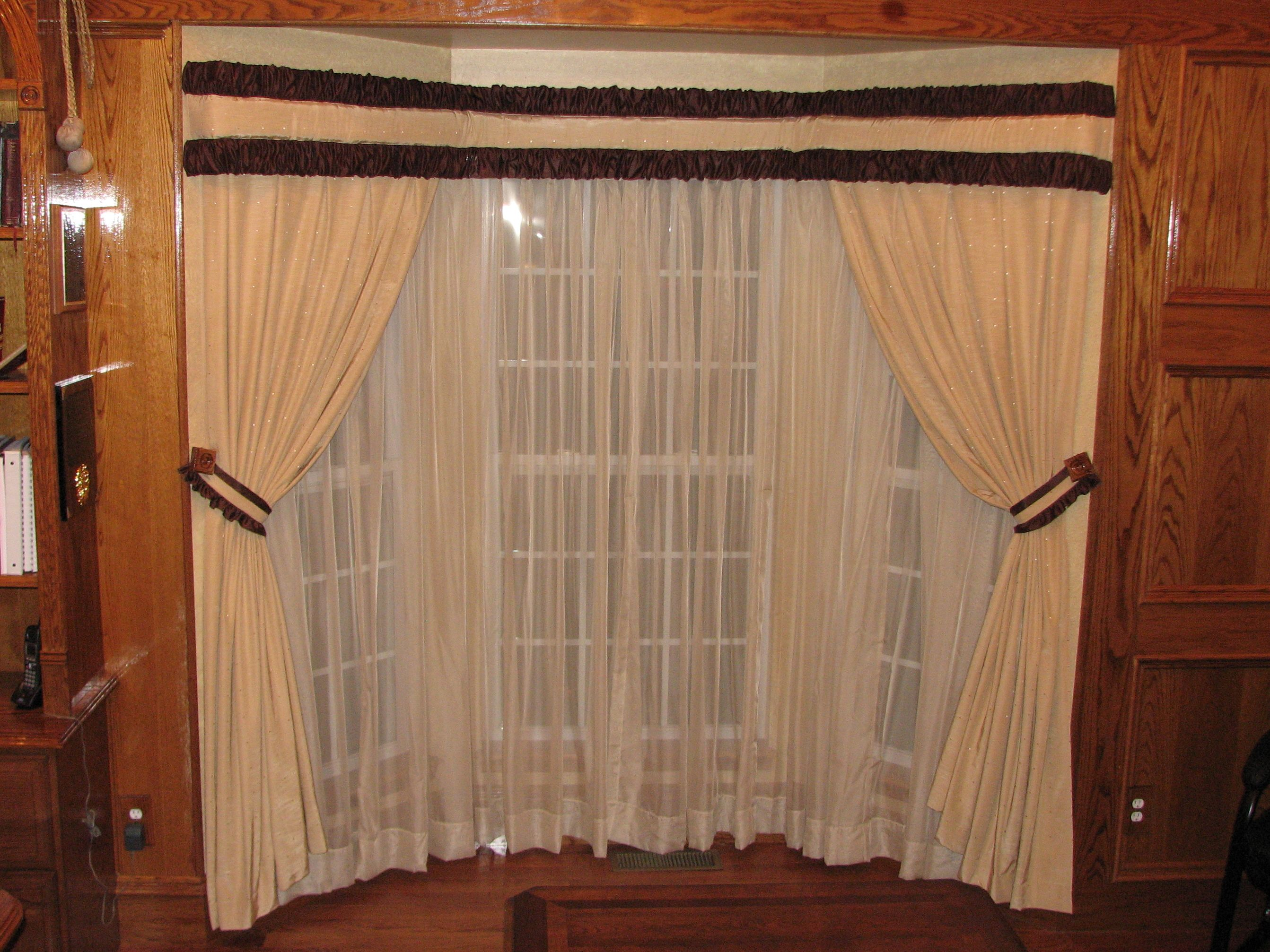 bay window drapes coordinated with sheers on a traverse rod