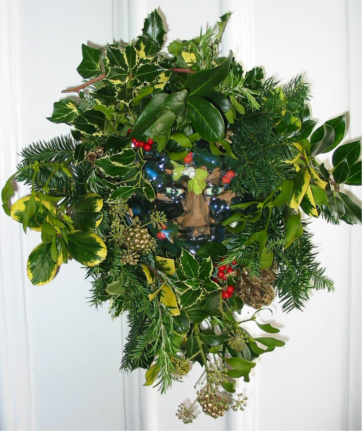 A ceramic Green Man mask put into the centre of the Christmas wreath for the door