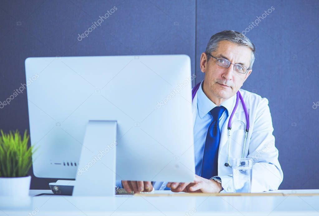 Portrait of senior doctor sitting in medical office  Stock Photo