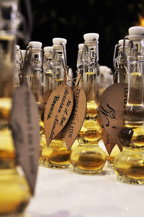 wedding gift/table assignment idea *use mini wine bottles instead? seating assignments on roman letter stamped leaf tags wrapped around bott...